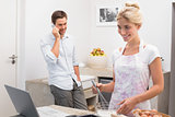 Woman preparing cookies while man on call in kitchen