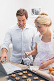 Couple preparing cookies while using laptop in the kitchen
