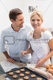 Happy young couple preparing cookies in kitchen