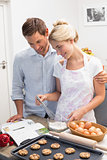 Couple looking at cook book and preparing cookies in kitchen