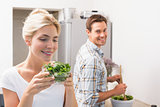 Woman holding bowl of leaves with man preparing salad in background in kitchen