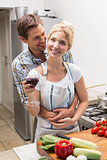 Portrait of a loving couple with wine glass in kitchen