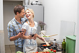 Loving young couple with wine glass in kitchen