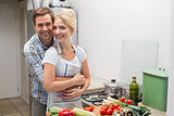 Portrait of a happy couple embracing while preparing food in kitchen