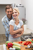 Portrait of a couple embracing while preparing food in kitchen