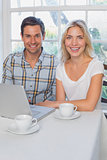 Portrait of a smiling young couple using laptop in kitchen