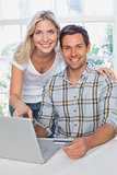 Smiling young couple doing online shopping at home
