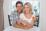 Loving couple reading text message together at home
