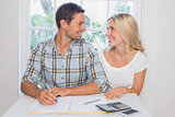 Couple with financial documents and calculator at home