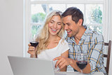 Couple with wine glasses using laptop at home
