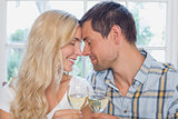 Loving couple with closed eyes holding wine glasses