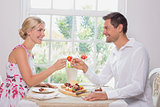Happy young couple toasting wine glasses over food
