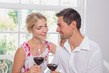 Happy loving young couple with wine glasses