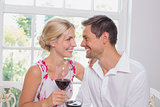 Happy loving couple with wine glasses looking at each other