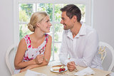 Loving couple with pastry looking at each other at dining table