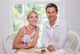 Loving young couple with pastry at dining table