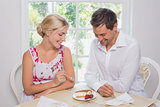 Happy young couple with pastry at dining table
