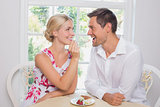 Loving woman feeding man pastry at dining table