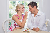Loving young woman feeding man pastry at home