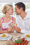 Loving couple with wine glasses looking at each other at dining table