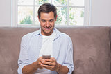 Casual man reading text message on sofa