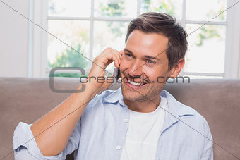 Casual man using mobile phone on sofa
