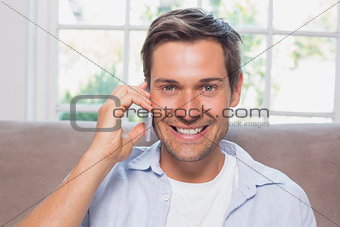 Close-up of a casual man using mobile phone on sofa