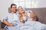 Relaxed loving couple with coffee cups in living room