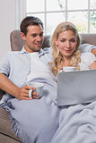 Relaxed couple with coffee cups using laptop on sofa