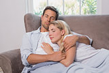 Loving young couple sleeping together on sofa
