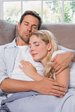 Relaxed loving couple sleeping together on sofa
