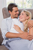 Loving couple looking at each other while lying on sofa