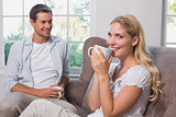 Couple with coffee cups sitting in living room