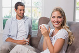 Relaxed couple with coffee cups sitting in living room