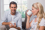 Portrait of relaxed couple with coffee cups in living room