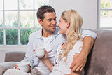 Relaxed loving couple with coffee cups sitting on sofa