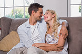 Relaxed loving couple sitting on sofa