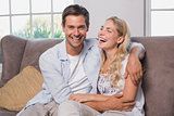 Relaxed cheerful loving couple sitting on sofa