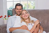 Portrait of relaxed happy loving couple sitting on sofa