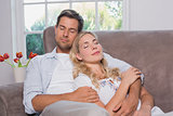 Relaxed loving couple sitting on sofa with eyes closed