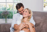 Relaxed loving man embracing woman in living room
