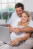 Relaxed casual couple using laptop in living room