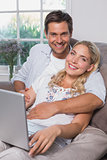 Portrait of a casual couple using laptop in living room