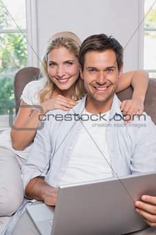 Portrait of casual couple using laptop in living room