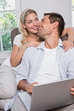 Happy casual couple using laptop in living room