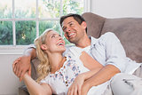 Cheerful casual couple laughing in living room