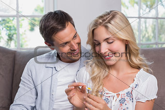 Happy couple looking at flower in living room