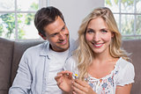 Happy young couple looking at flower in living room