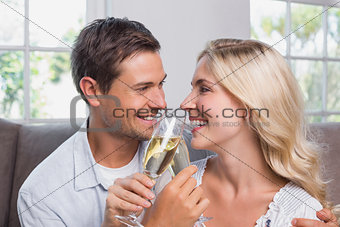 Cheerful loving couple with champagne flutes at home