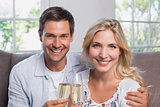 Cheerful young couple with champagne flutes at home